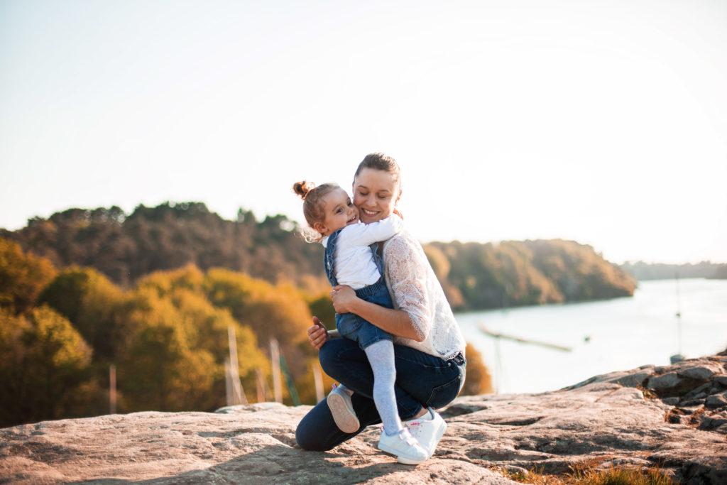 Petite fille prenant sa maman dans ses bras sur des rochers face à la mer