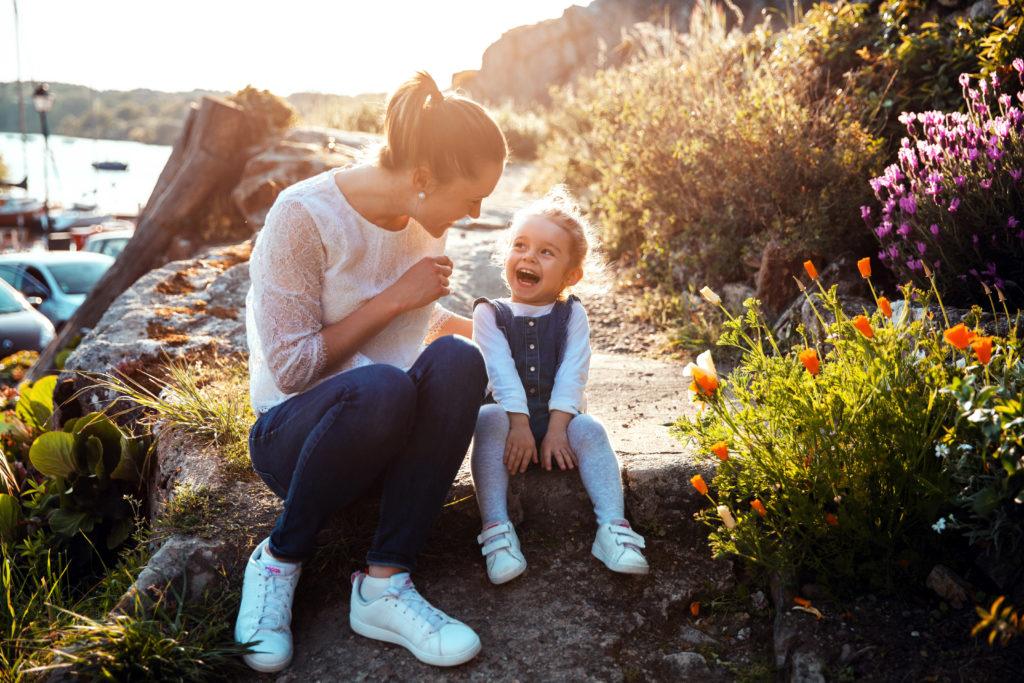Maman rigolant avec sa petite fille lors d'un coucher de soleil