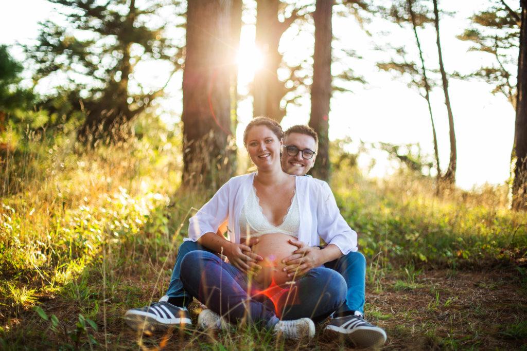 Couple assis dans une fôret mettant leur mains sur le ventre de la femme enceinte pendant un coucher de soleil