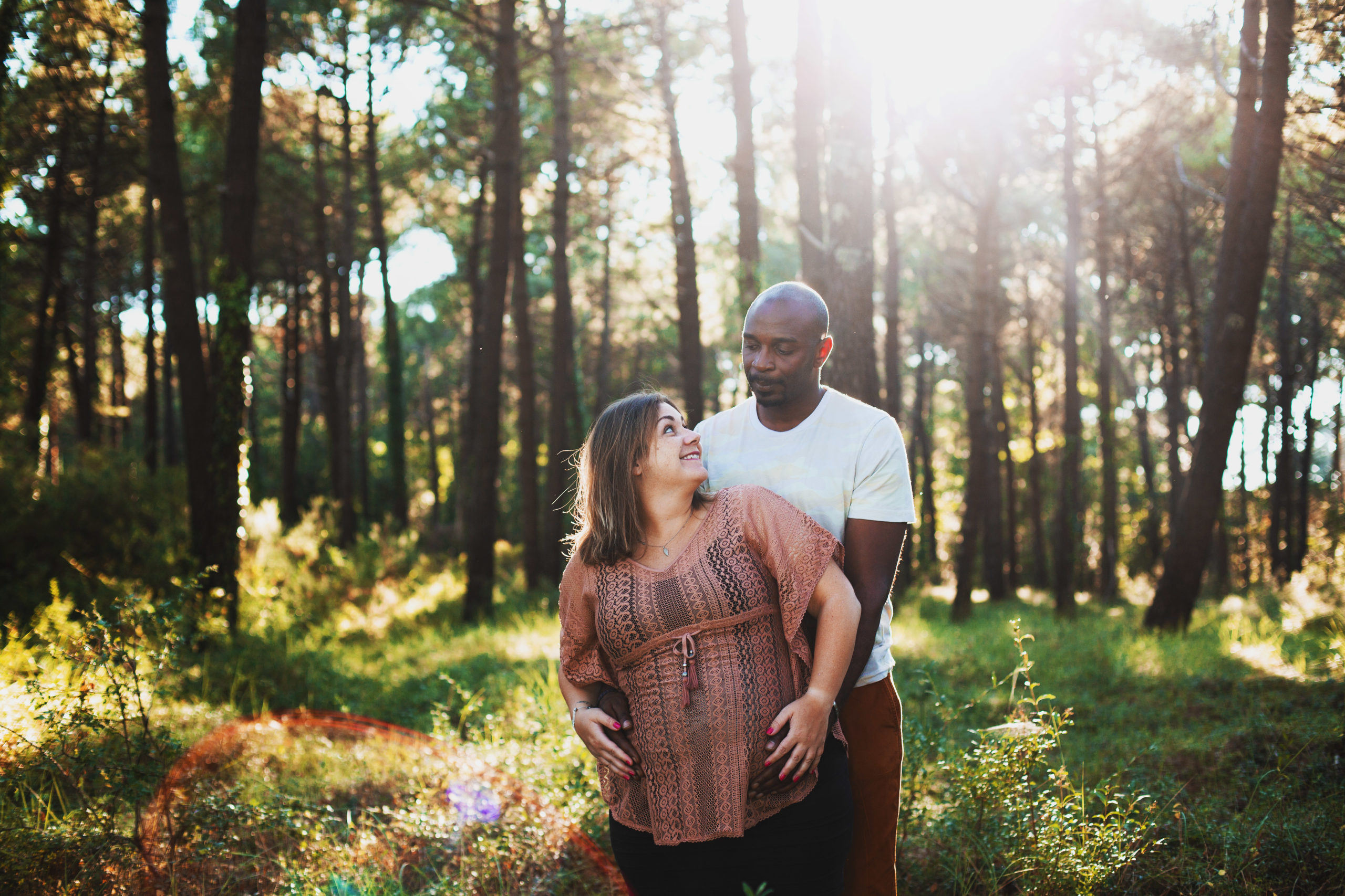 Femme enceinte et homme noir se regardent dans une fôret pendant le coucher de soleil