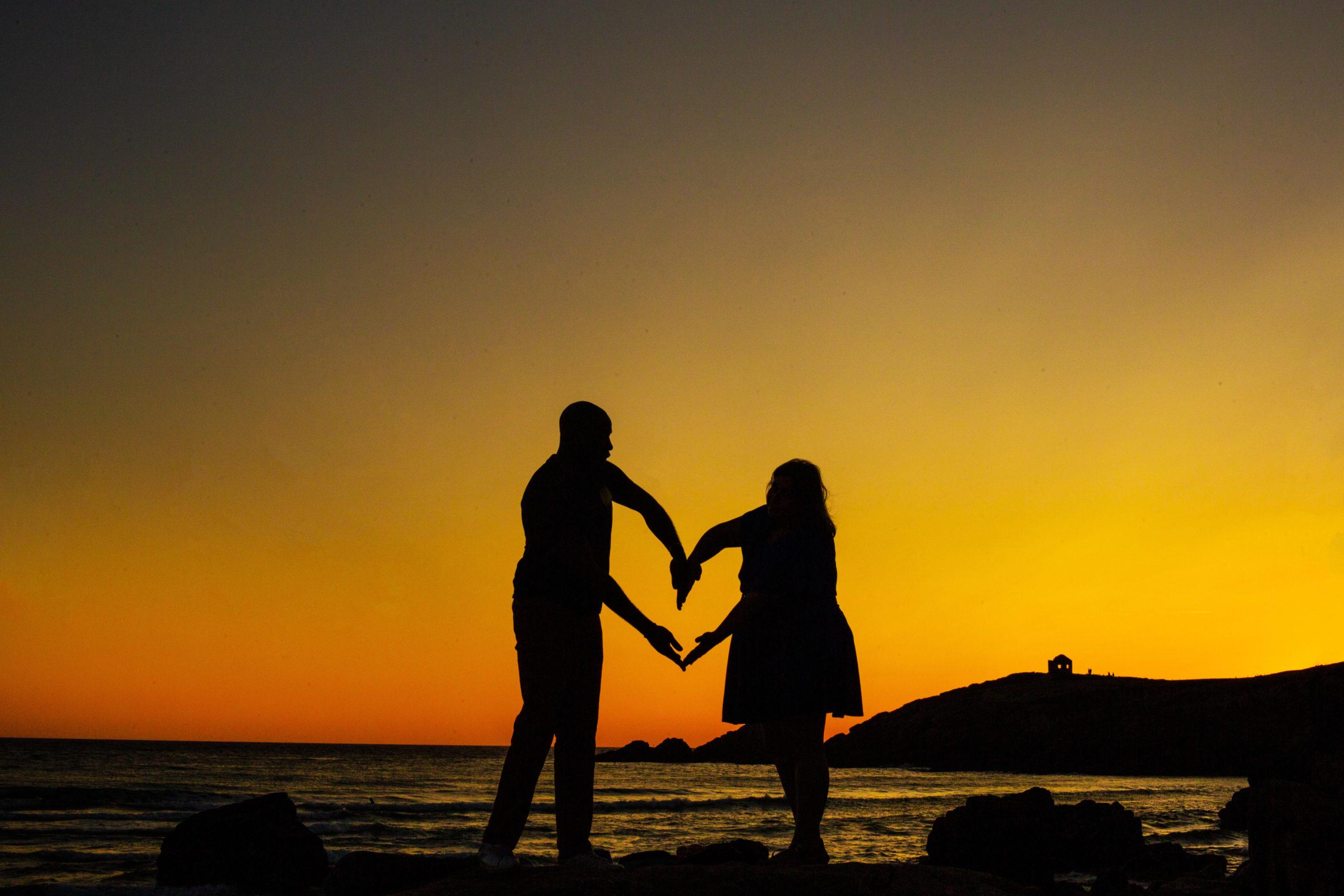 Couple formant un coeur avec leur bras en faisant les ombres chinoises pendant le coucher de soleil sur des rochers