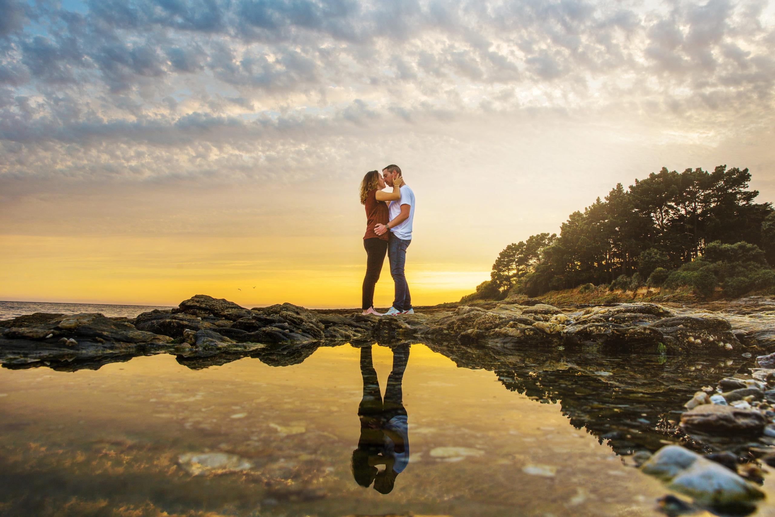 Couple qui s'embrassent sur les rochers avec leur reflet dans l'eau pendant le coucher de soleil
