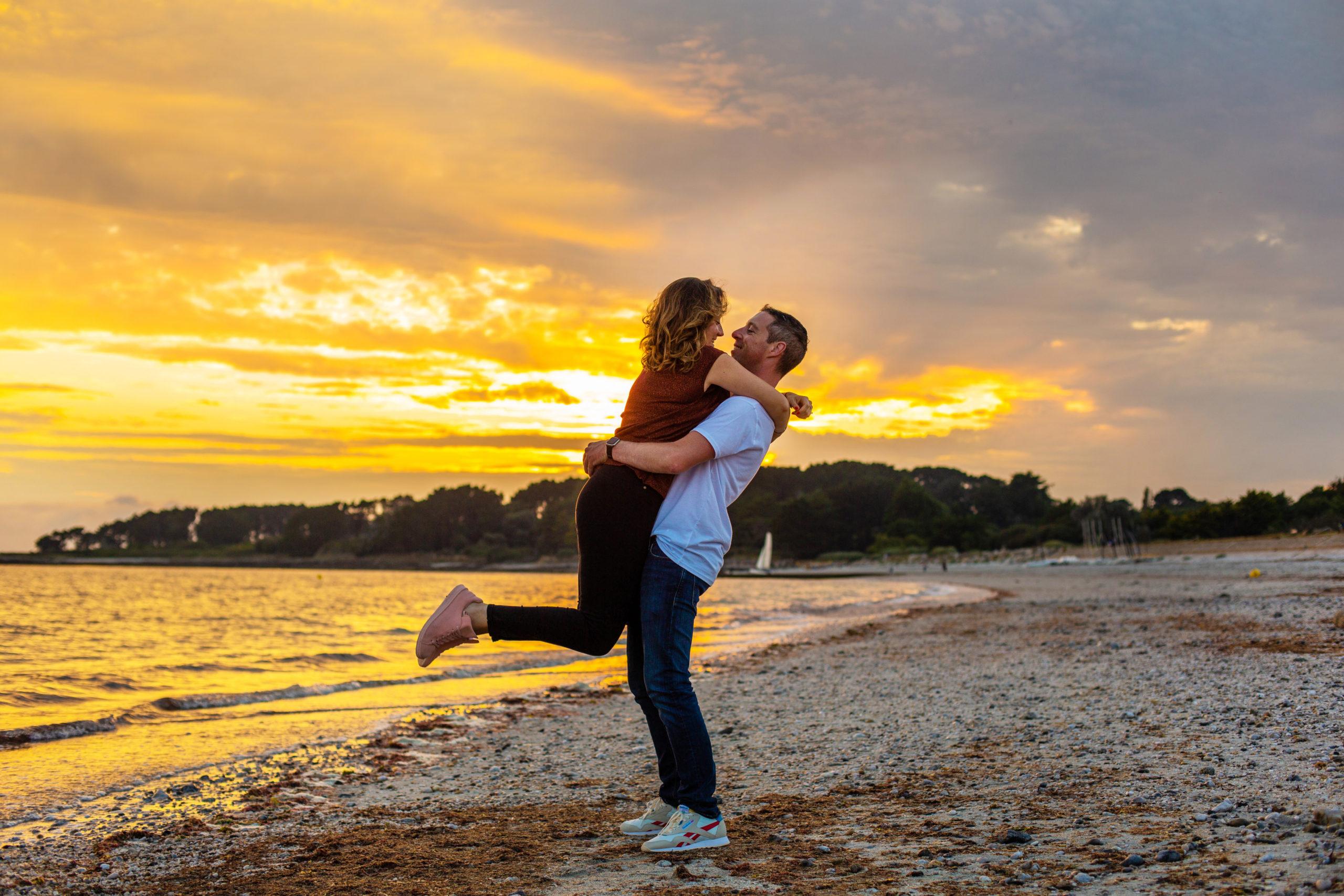 Une femme se jetant dans les bras de son homme sur la plage pendant le coucher de soleil