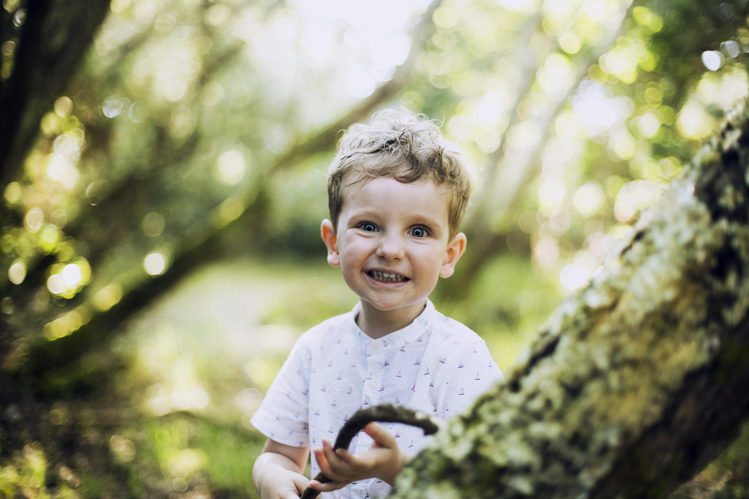 Petit garçon avec une chemise blanche fait les gros yeux tenant un baton dans ses mains dans une fôret