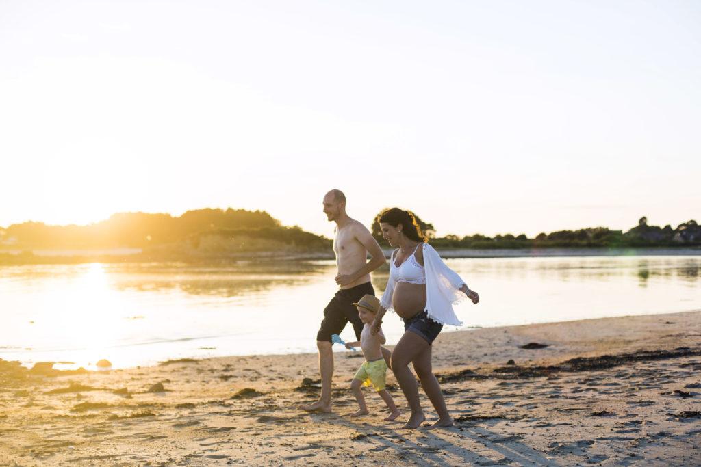 Un papa, une maman enceinte et un petit garçon courent sur la plage pendant un coucher de soleil