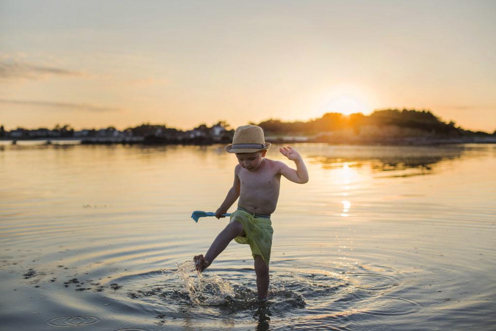 Petit garçon éclaboussant dans l'eau avec son rateau pendant un coucher de soleil