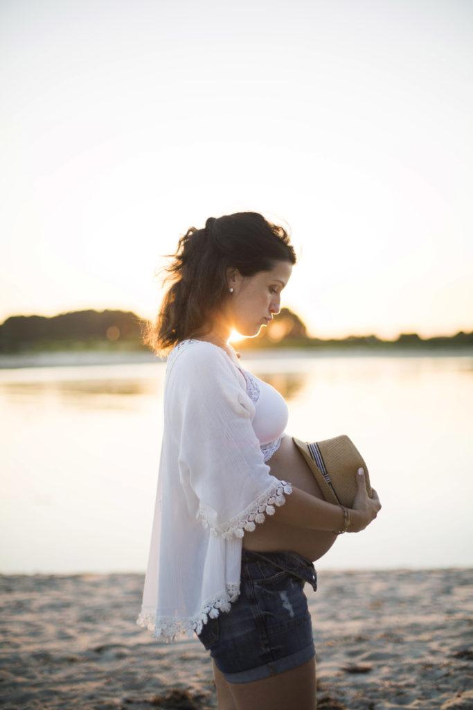 Femme enceinte poser un chapeau en paille sur son ventre sur la plage pendant le coucher de soleil
